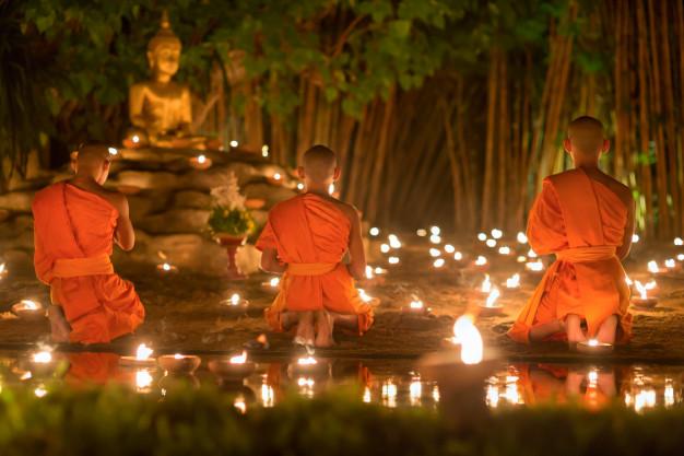 moine bouddhiste méditant devant une statue de bouddha thailand